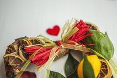 Rieten kroon met hart-vormig, verfraaid met bladeren, citroen, droge citroen Royalty-vrije Stock Afbeelding