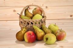 Rieten mand met appelen en peren op houten achtergrond Stock Foto's