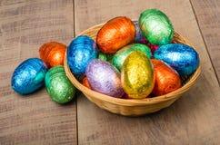 Rieten mand met de eieren van de foliechocolade Stock Afbeeldingen