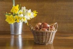 Rieten mand met de eieren van de kip en boeket van witte en gele gele narcissen op mooie houten achtergrond royalty-vrije stock fotografie