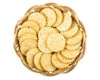 Rieten mand met ronde die crackers op wit worden geïsoleerd Stock Afbeelding