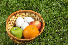 Rieten mand met vruchten en eieren op gras Stock Foto's