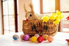 Rieten mand, stropaashaas en gele narcissen, gehaakte eieren Stock Afbeeldingen