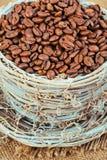 Rieten mok met koffiebonen op een achtergrond van jute Stock Foto