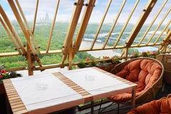 Rieten stoelen en lijst bij terras Stock Afbeelding