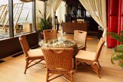 Rieten stoelen en lijst in restaurant Stock Fotografie
