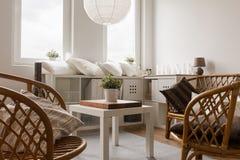 Rieten stoelen en witte lijst Stock Afbeeldingen