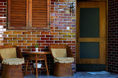 Rieten terrasstoelen en lijst dichtbij Stock Fotografie