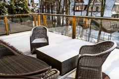 Rieten tuinmeubilair op een houten, sneeuwterras met glasbalustrades, in de achtergrondbomen en de huizen royalty-vrije stock foto