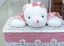 Rieten wasmand met een roze doek en een stuk speelgoed stock afbeelding