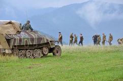 Rievocazione storica della battaglia di guerra mondiale 2 - il veicolo ed i soldati di trasporto corazzati si sono vestiti in uni Immagine Stock Libera da Diritti
