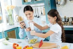 Rifinitura ispirata della ragazza e della madre che produce insalata Fotografia Stock