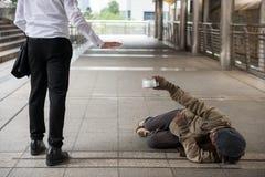 Rifiuti dell'uomo d'affari che danno soldi all'uomo senza tetto fotografia stock libera da diritti