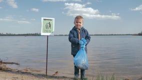 Rifiuti di inquinamento di problema ambientale, ritratto del ragazzo del piccolo bambino con la borsa di immondizia a disposizion stock footage