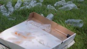 Rifiuti e bottiglie di plastica su erba Immondizia sparsa in parco pubblico, inquinamento ambientale archivi video
