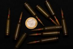 Rifle ammo around one euro coin on black background. Symbolizes the war for money and one of the world`s problems.  stock photography