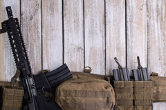 Rifle and army belt with ammo on table Royalty Free Stock Photos