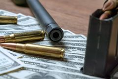 Rifle barrel, magazine and cartridges on money. Concept for crime, contract killing, paid assassin, terrorism, war. Global arms trade, weapons sale. Illegal royalty free stock images