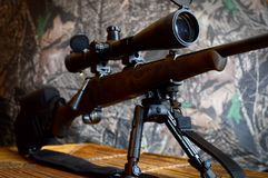 Rifle On Bipod. Closeup side view of a rifle on a bipod with camo background Royalty Free Stock Photography