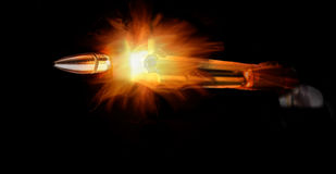 Rifle And Bullet. With bright flames on black background Royalty Free Stock Images