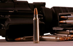 Rifle bullets. Military rifle ammo with a modern assault rifle in the back ground Stock Photo