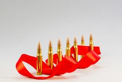 Rifle bullets. Brass Sleeve. With a red ribbon. On a white backg Royalty Free Stock Image