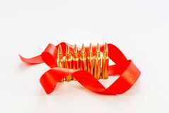 Rifle bullets. Brass Sleeve. With a red ribbon. On a white backg Stock Photo