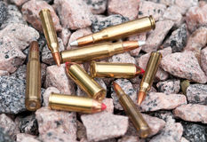 Rifle bullets on rocky ground Stock Photos