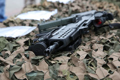 Rifle on the camouflage net Stock Photos