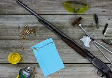 Rifle with cleaning supplies and Firearm Cleaning checklist on rustic wooden background Stock Images
