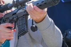 Rifle con una vista óptica en manos de hombres imagen de archivo