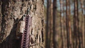 Rifle de asalto colocado al lado de un árbol en el bosque almacen de metraje de vídeo