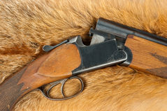 Rifle on fur Stock Images