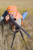 Rifle hunter in Prone Position. A big game hunter in prone position working the bolt on his rifle Stock Images