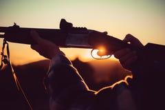 Rifle Hunter Silhouetted no por do sol bonito Caçador com o rifle poderoso com os animais da mancha do espaço Puxou o disparador fotografia de stock