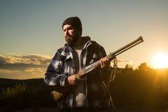 Rifle Hunter Silhouetted no por do sol bonito Caçador na época de caça da queda A caça é a prática da matança ou imagem de stock royalty free