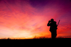 Rifle Hunter at Sunrise. A big game hunter with rifle glasses for game silhouetted in the sunrise Royalty Free Stock Photo