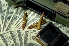 Rifle, magazine and cartridges on hundred dollar bills. Concept for crime, contract killing, paid assassin, terrorism. War, global arms trade, weapons sale stock photography