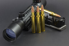 A rifle scope, ammo and a clip. A rifle scope with ammo and a clip Royalty Free Stock Photo