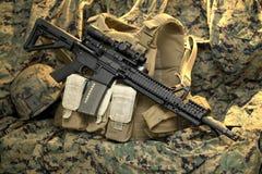 Rifle tático que descansa na veste Imagens de Stock Royalty Free