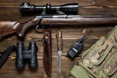 Rifle y munición de la caza en un fondo de madera Foto de archivo