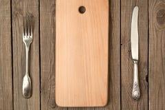 Rifled Brett, alte Gabel und Messer Stockfotos