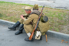 Rifleman of Red Army. Dnepropetrovsk, Ukraine - September 14, 2013: Group of unidentified re-enactors dressed as Soviet soldiers in greatcoat resting Stock Images