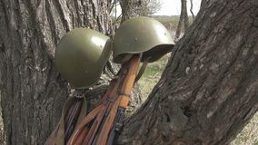 Rifles and helmets of the Soviet army of the Second World War. Rifles and a helmet of the Soviet army of the times of the second world near the tree stock video
