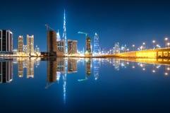 Riflessione affascinante dei grattacieli più alti nel distretto della baia di affari durante la notte calma Il Dubai, Emirati Ara Fotografia Stock