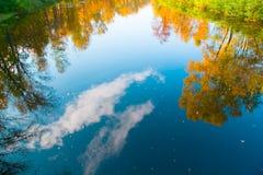 Riflessione degli alberi di autunno e del cielo, nubi nel fiume Fotografia Stock