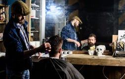 Riflessione del barbiere che disegna capelli del cliente barbuto con il pettine Cliente dei pantaloni a vita bassa che ottiene ac immagini stock