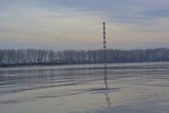 Riflessione del camino di industria nel fiume Fotografie Stock