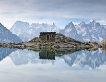 Riflessione del lago delle montagne e della capanna Immagine Stock