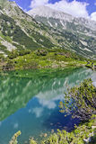 Riflessione del picco di Vihren nel lago Okoto, montagna di Pirin Immagini Stock